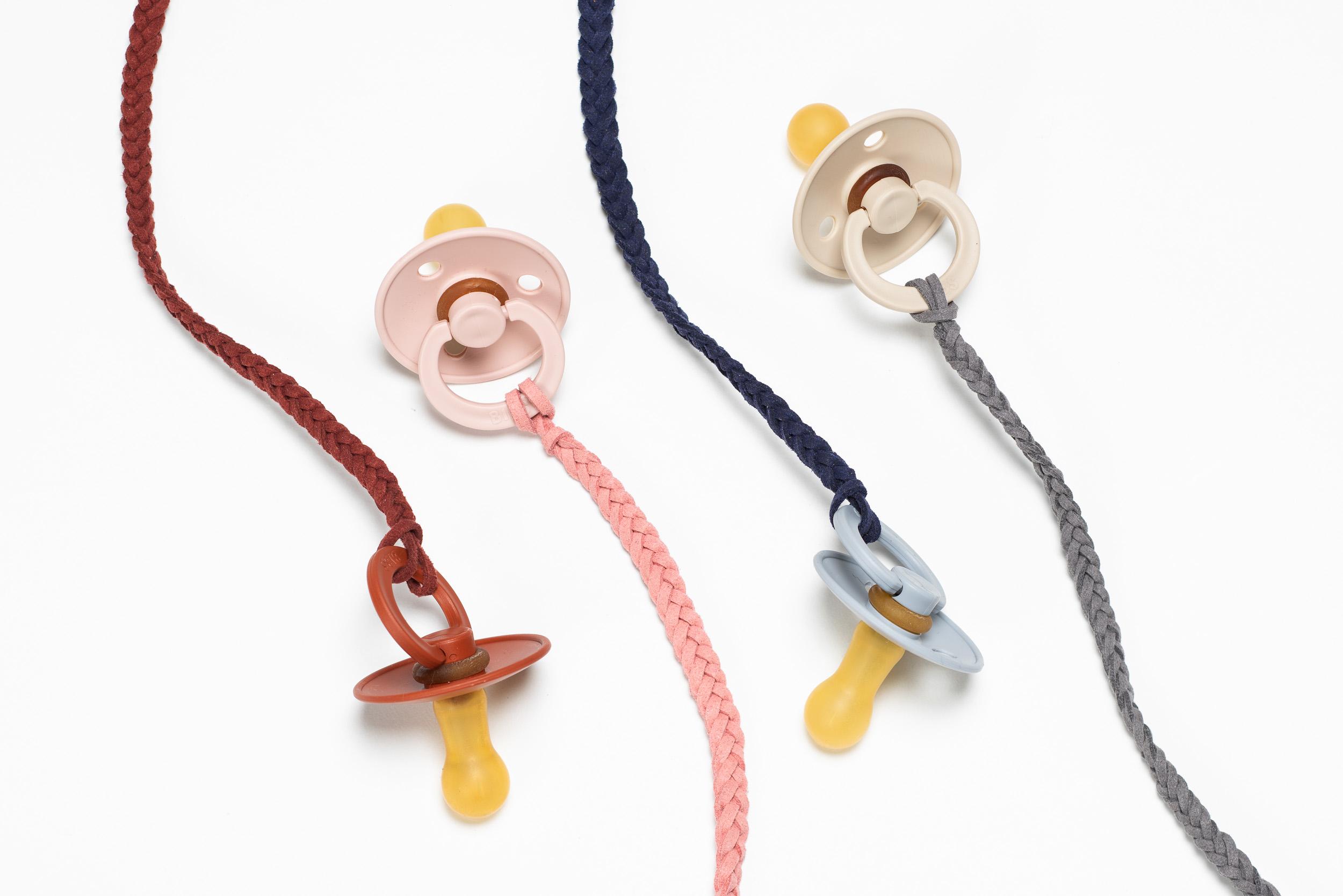 Die handgemachten Schnullerbänder werden von Tiny Totsies aus Lederbändern geflochten.